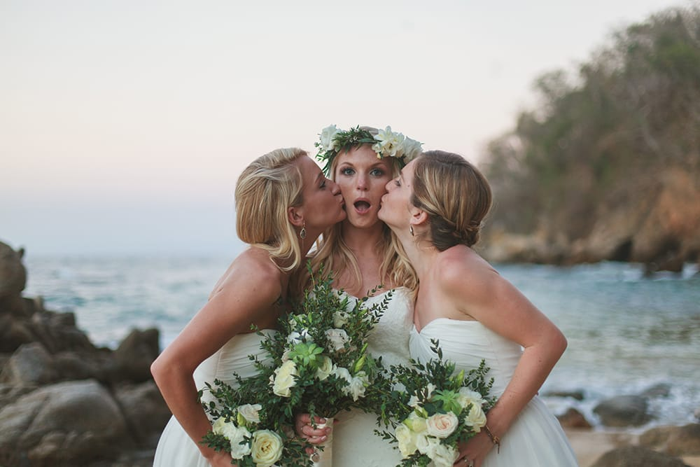 Brides with bridesmaids in group photo from the professional onsite photographers at Adventure Weddings