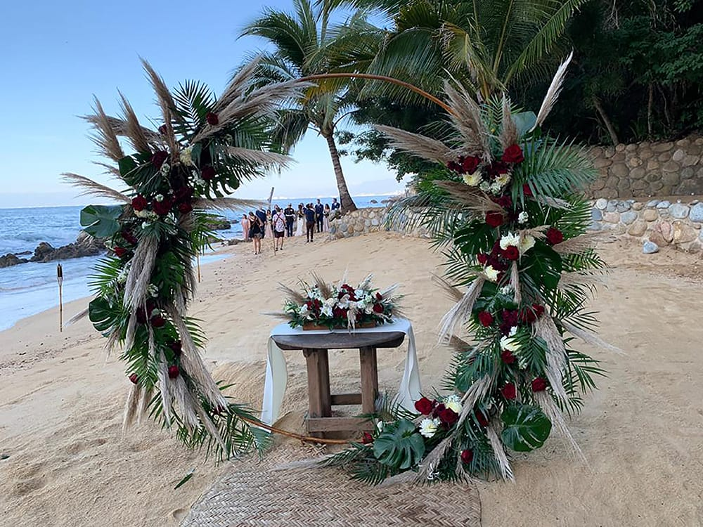 Signing table with floral arrangement under a circular arch arranged with red and white roses and tropical greenery for a destination wedding ceremony set up by Adventure Weddings