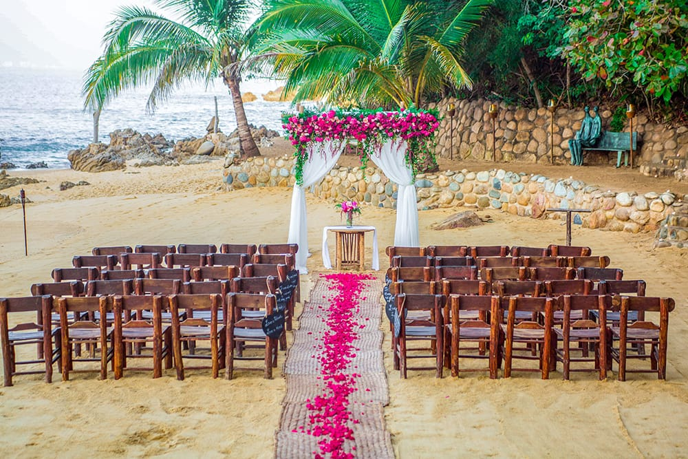 A simple arch draped with white fabric and plenty of bright pink roses over a small signing table with a simple floral arrangement for beach wedding ceremony set up by Adventure Weddings