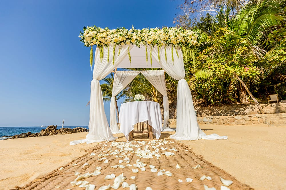 A simple arch draped with white fabric and plenty of white roses over a small signing table with a simple floral arrangement for beach wedding ceremony set up by Adventure Weddings