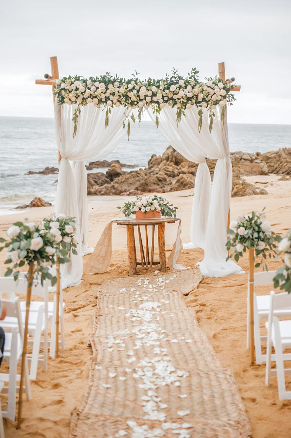 Wedding arch with full white rose garland and signing table with floral arrangement facing the water for a beach wedding ceremony by Adventure Weddings