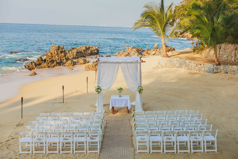 Simple white wedding ceremony set up with burlap aisle runner facing the ocean shore by Adventure Weddings