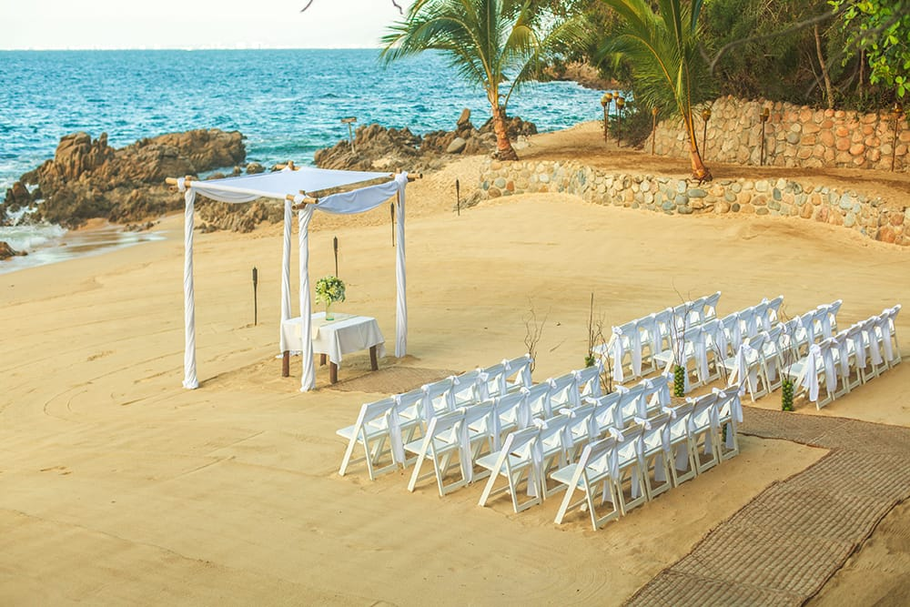 Beach wedding ceremony set up facing the water with burlap aisle white chairs and a draped Chuppah by Adventure Weddings.