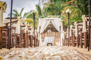 A Chuppah draped with soft white fabric and neutral rose garland behind an aisle lined with lanterns and white flower petals for a wedding ceremony set up by Adventure Weddings