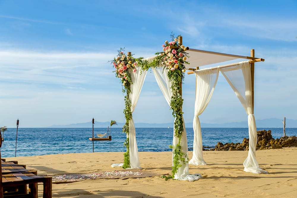 Tropical coloured flowers hang from a Chuppah draped with white fabric for a destination wedding ceremony set up by Adventure Weddings