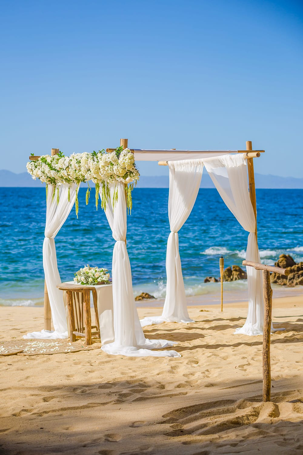 Wedding chuppah set up for outdoor beach wedding with bohemian flower and fabric design by Adventure Weddings