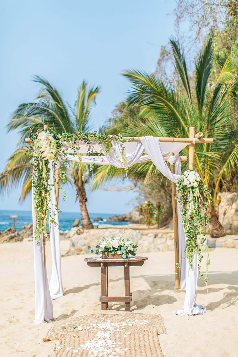 Chuppah on beach with greenery and white roses draping off set up by Adventure Weddings for small wedding ceremony