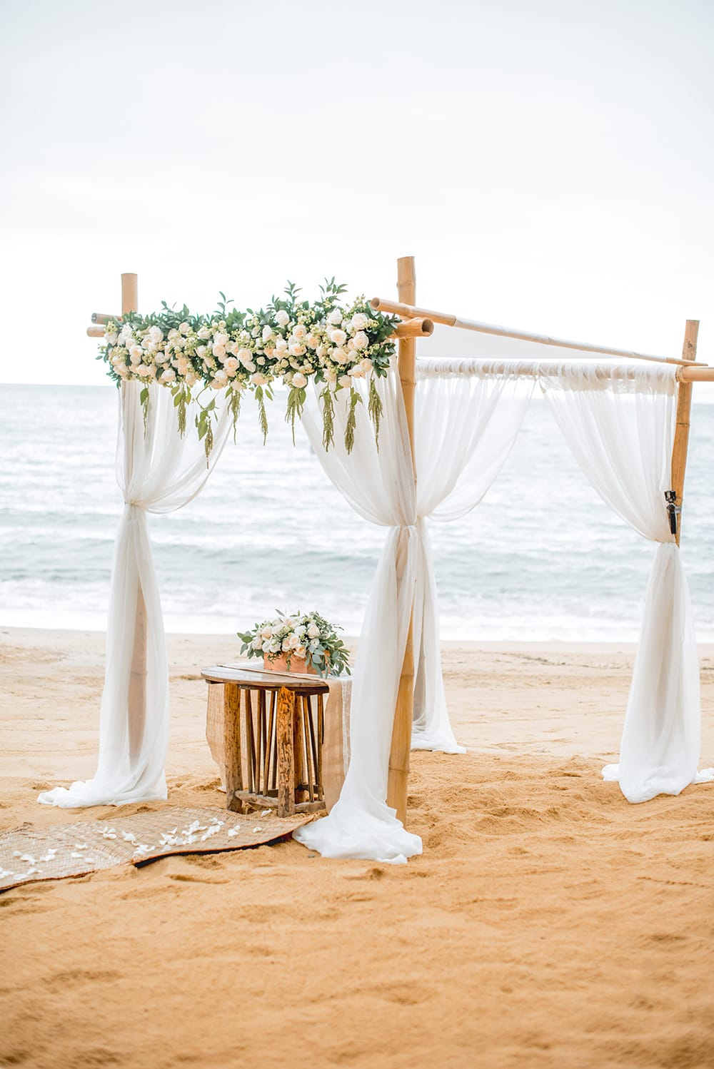 Beach set up for a wedding ceremony by Adventure Weddings with Chuppah draped with white fabric, accented by hanging floral arrangements.