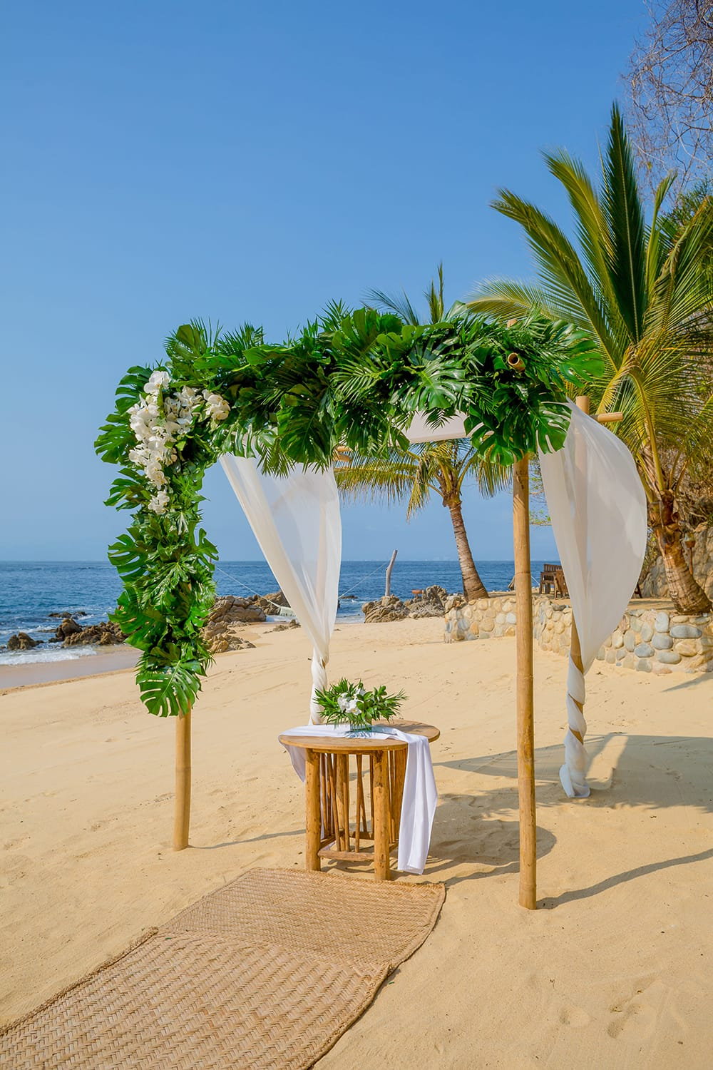 Small signing table under a wooden arch with large tropical garland for outdoor destination wedding ceremony by Adventure Weddings