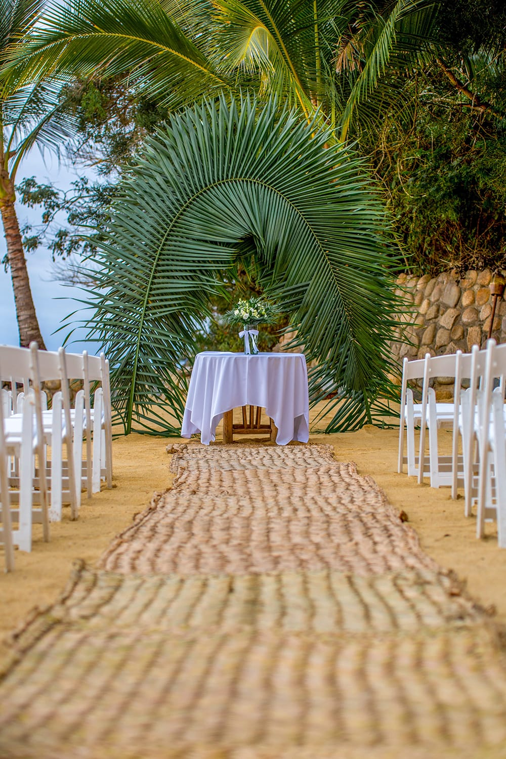 Signing table for outdoor beach wedding ceremony with floral centerpiece set up by Adventure Weddings.