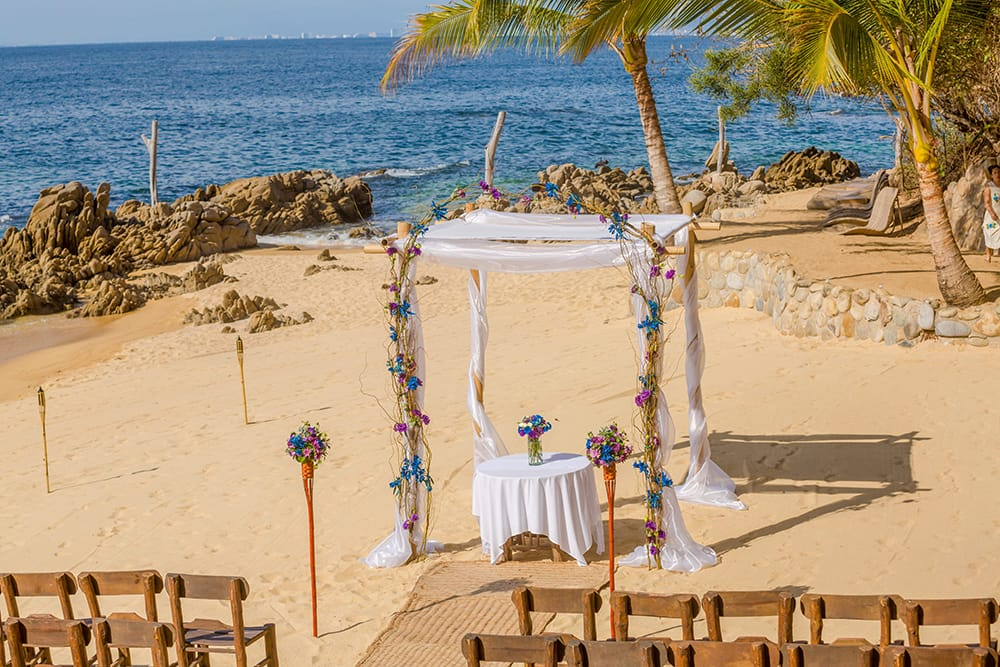 Chuppah with white fabric and vines crawling up the sides surrounds a signing table with small colourful floral arrangement by Adventure Weddings