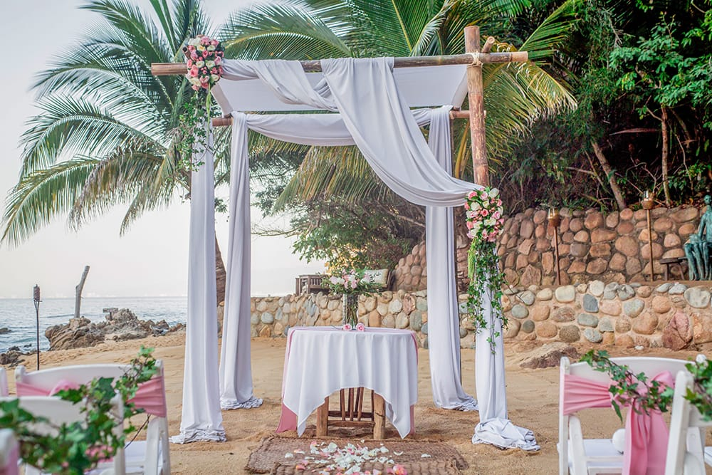 Wedding chuppah draped with white fabric and pink rose accents with signing table underneath for a beach wedding by Adventure Weddings