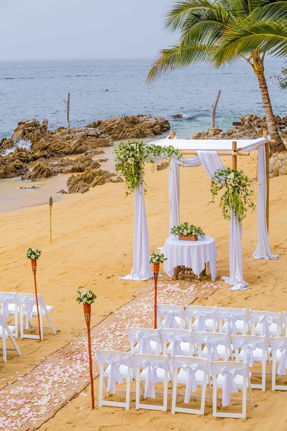 A simple Chuppah with sheer fabric and a burlap aisle running scattered with flower petals for a destination wedding ceremony set up by Adventure Weddings