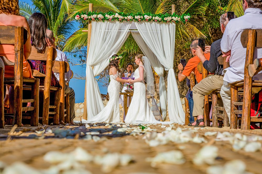 Photo of couple exchanging vows during same-sex destination wedding ceremony by the photographers at Adventure Weddings