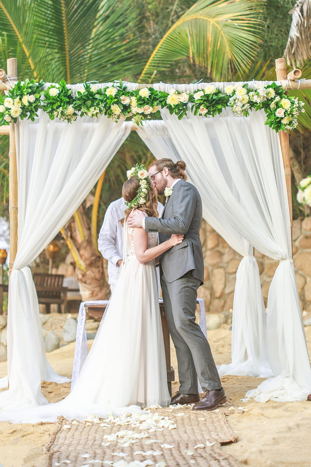 Couple sharing first kiss as married couple during destination wedding ceremony in Mexico