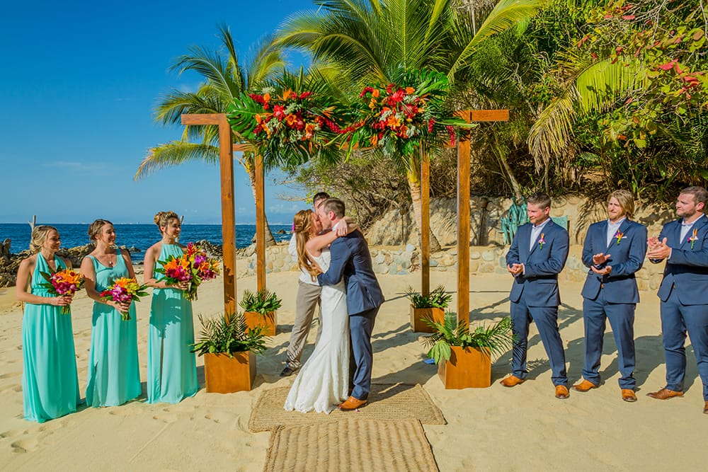 Photo of couples first kiss at destination wedding captured by the onsite photographers at Adventure Weddings