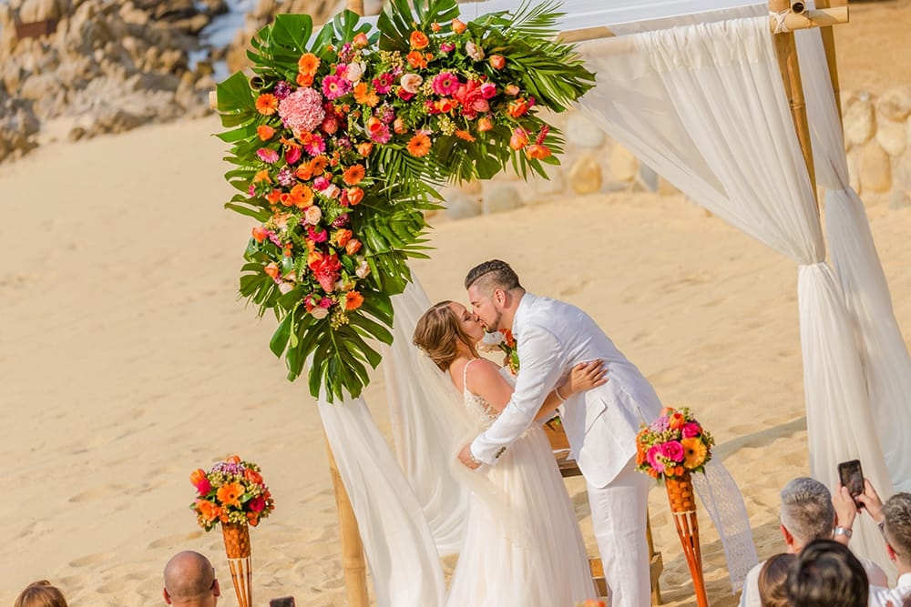 Couples first kiss as husband and wife during beach ceremony as part of their destination wedding in Mexico