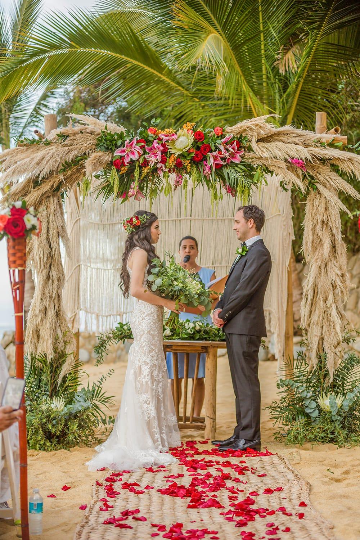 Beach wedding ceremony under tropical bohemian arch at destination wedding venue in Mexico