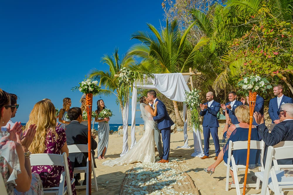 Guests applauding couples first kiss as husband and wife at their destination wedding ceremony in Mexico coordinated by Adventure Weddings