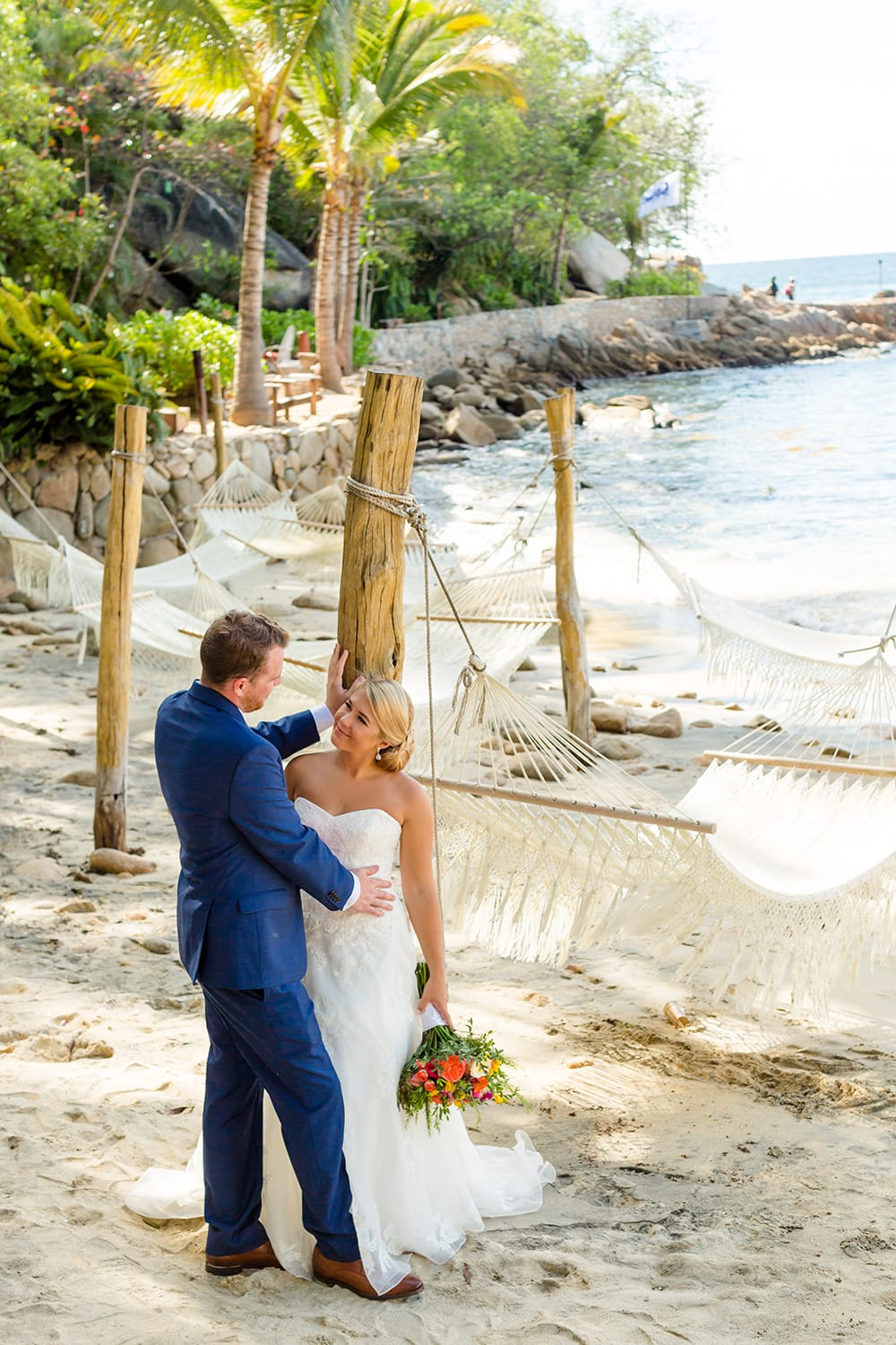 Adorable first look taking place in front of hammocks and the ocean at Adventure Weddings private beach venue