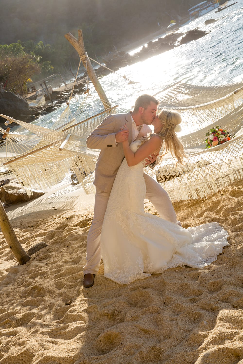 Romantic kiss in front of the Pacific ocean during the first look at a destination wedding in Mexico