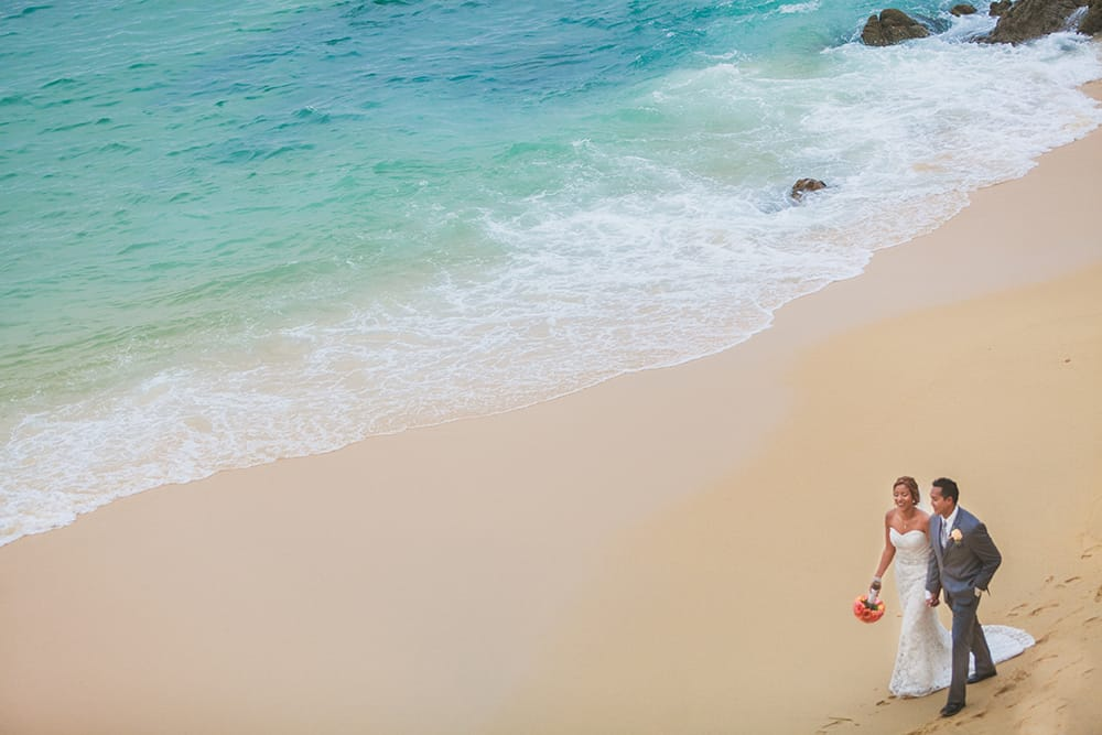 A drone captures an image of a bride and groom walking along the sand during their first look at their destination wedding in Mexico