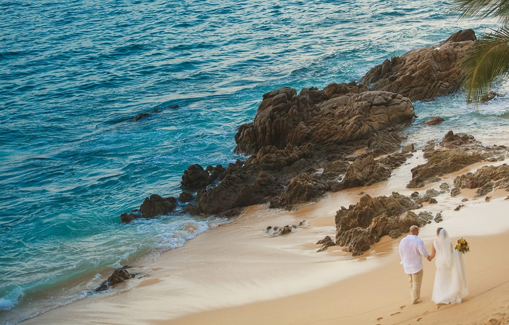 Drone footage of a couple walking along the beach during their intimate first look at their Mexican destination wedding