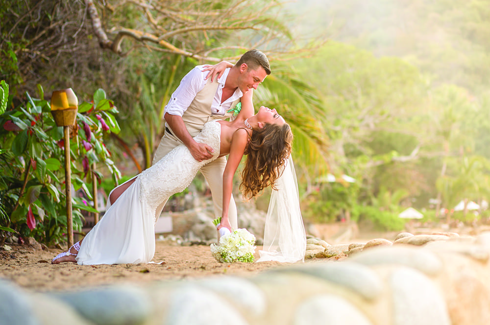Groom dips bride during first look on the beach at Adventure Weddings' destination wedding venue in Mexico