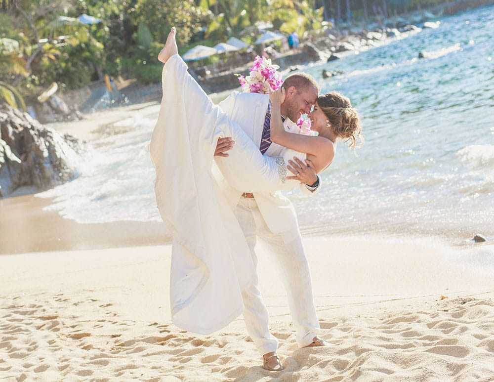 Groom picks up bride during first look at Adventure Wedding destination beach venue in Mexico