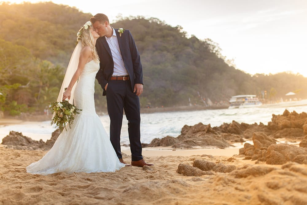 Bride and groom share a kiss during their first look on a stunning private beach venue in Mexico