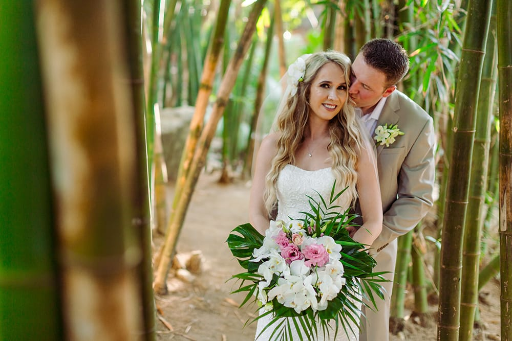 Groom kissing bride's cheek in a tropical forest during their first look