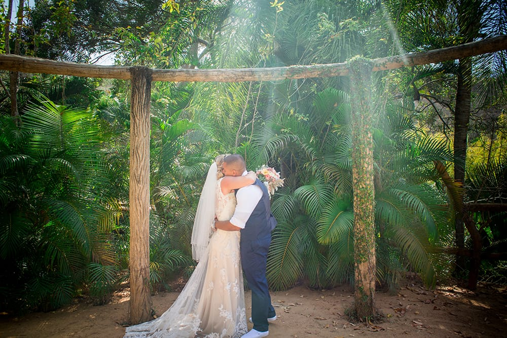 The bride and groom embracing during first look on a tropical beach venue in Mexico