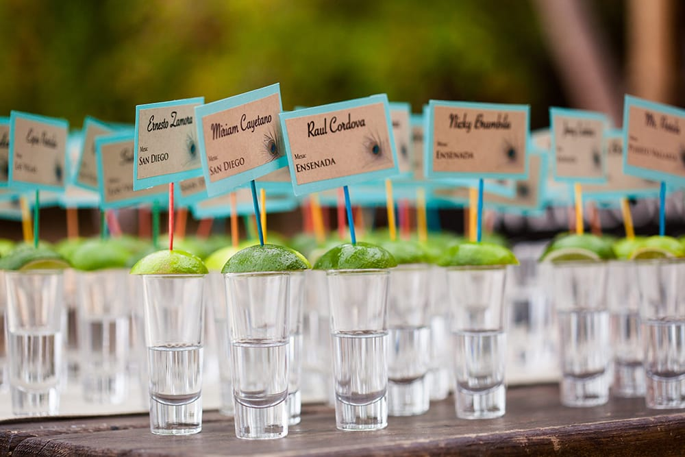 Silver tequila shot as wedding favours and seating chart for guests of a destination wedding in Mexico