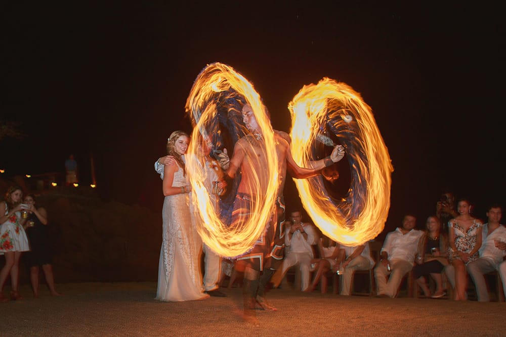 Fire dancer wowing guests at destination wedding during nighttime beach reception