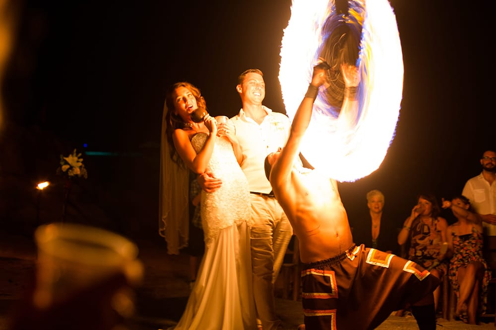 Couple enjoying fire dancing show at their destination wedding reception coordinated by Adventure Weddings