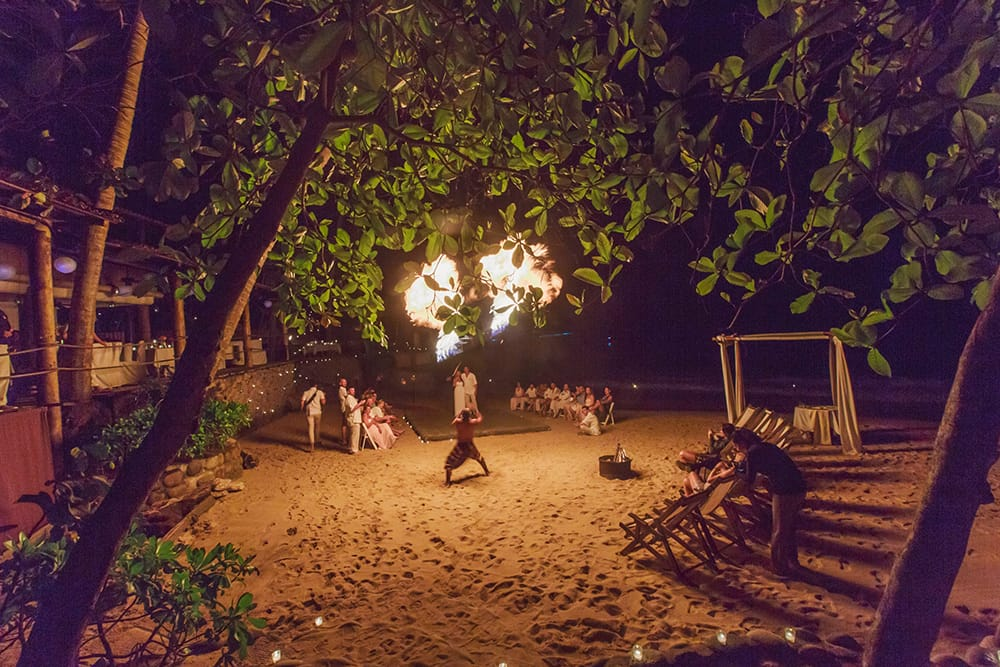 Fire dance providing show during destination wedding reception coordinated by Adventure Weddings