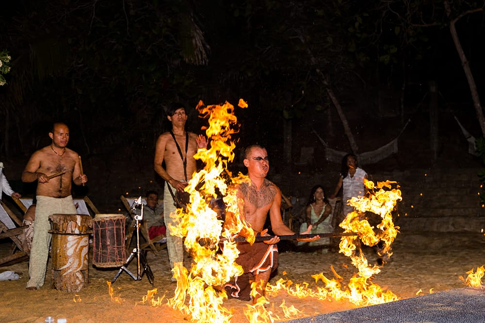 Fire dancers and drummers providing wedding entertainment to beach destination wedding