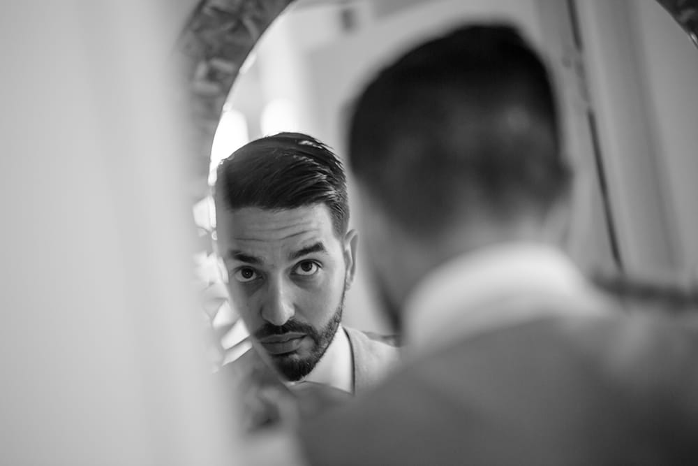 Groom taking a final look in the mirror before walking down the aisle at his destination wedding in Mexico