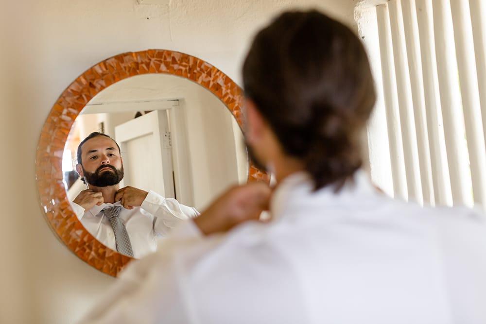 Groom fixes his tie in the mirror before his destination wedding ceremony in Mexico