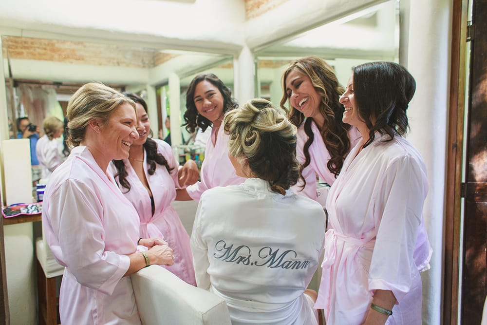 Bridesmaids compliment the bride as she gets ready in stunning bridal suite at Adventure Weddings destination venue