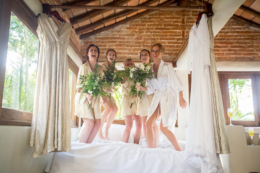 Brides and bridesmaid jumping on the bed before wedding ceremony in Mexico