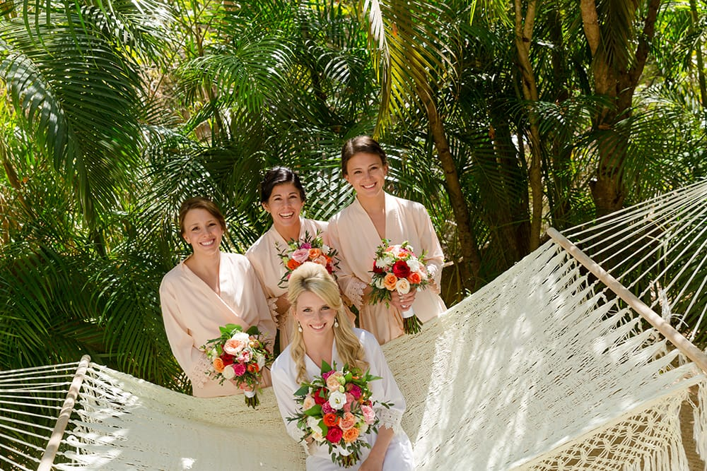 Bride and bridesmaid on hammock at destination wedding venue in Mexico before the ceremony