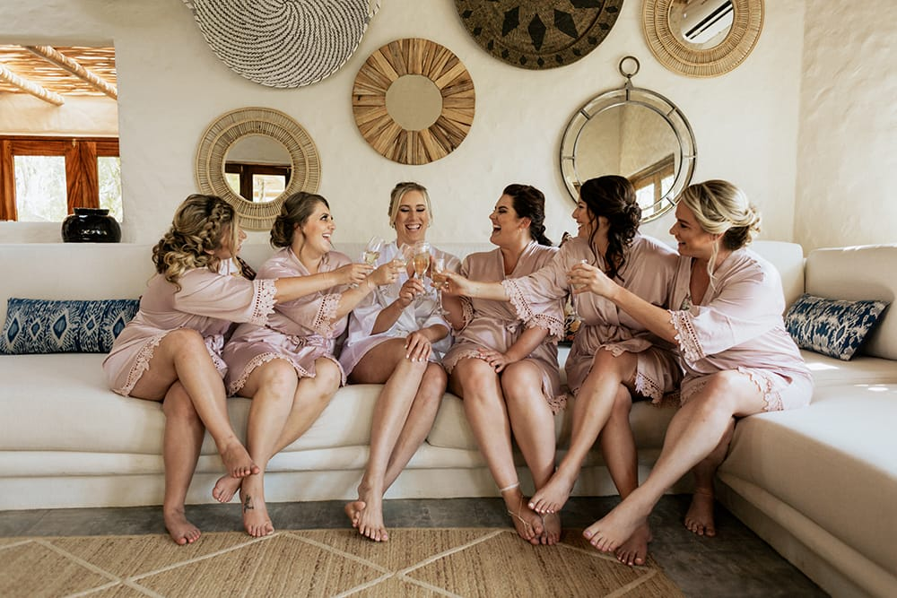 Bride toast with her bridal party prior to the ceremony on the comfortable sofa in the onsite bridal suite