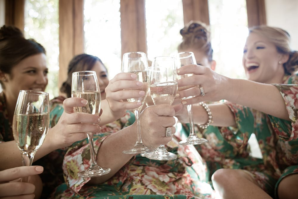 Bridesmaids toasting the bride with champagne while getting ready for her destination wedding with Adventures Weddings