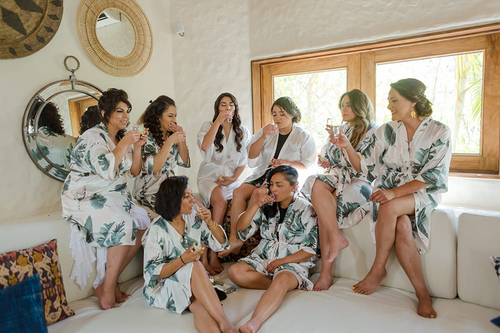 Bridesmaids enjoying a glass of champagne with the bride on the sofa in Adventure Weddings bridal suite