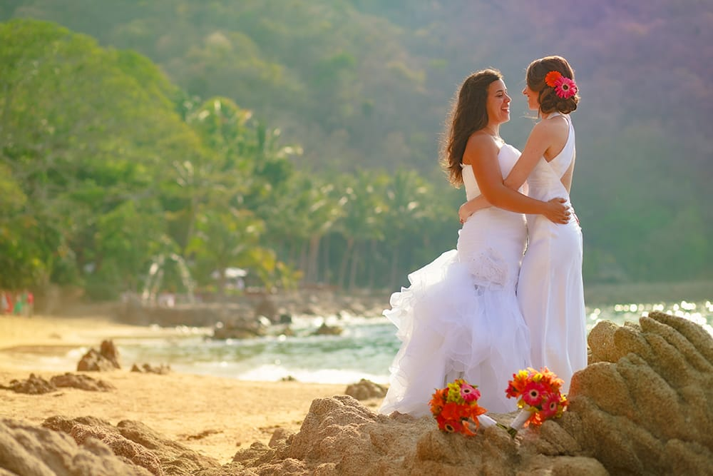Brides embrace during their first look on a private beach in Mexico