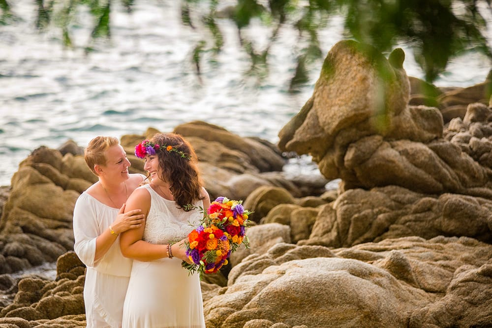 Brides enjoying their first look atop rock formation on a tropical Mexican beach