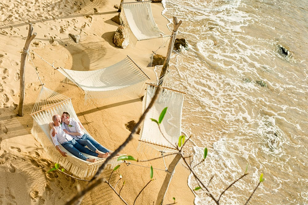 Grooms sharing a snuggle on a hammock following their first look at their destination wedding