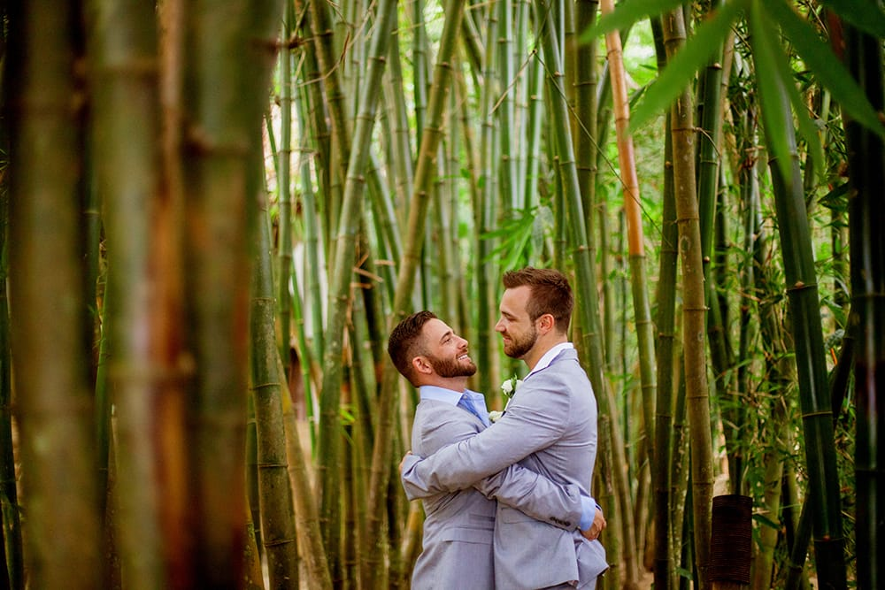 Grooms embrace during first look surrounded by palm trees on a tropical destination wedding venue in Mexico