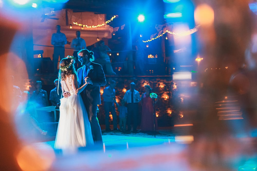 Candid photo of bride and groom sharing first dance at destination wedding